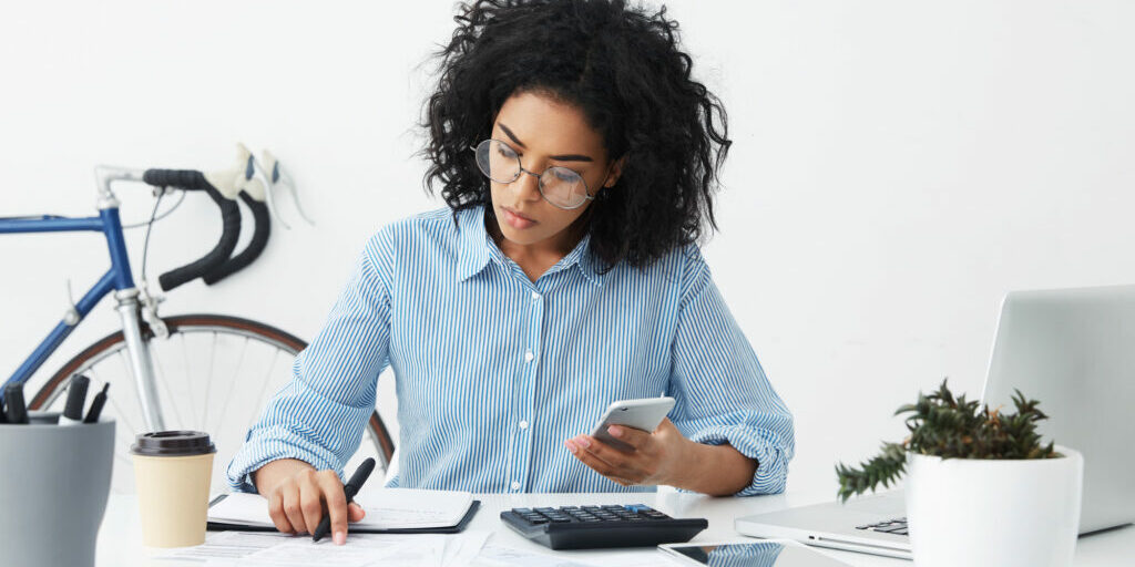 Business, career and job concept. Successful young dark-skinned female entrepreneur holding mobile phone, dialing number, looking at piece of paper, busy doing accounts, sitting at her workplace
