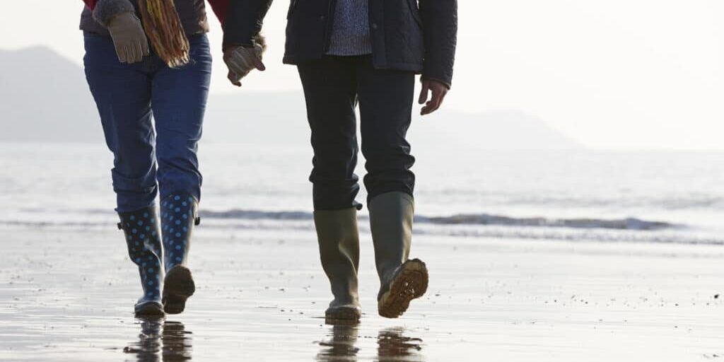 Close Up Of Senior Couple Walking Along Winter Beach